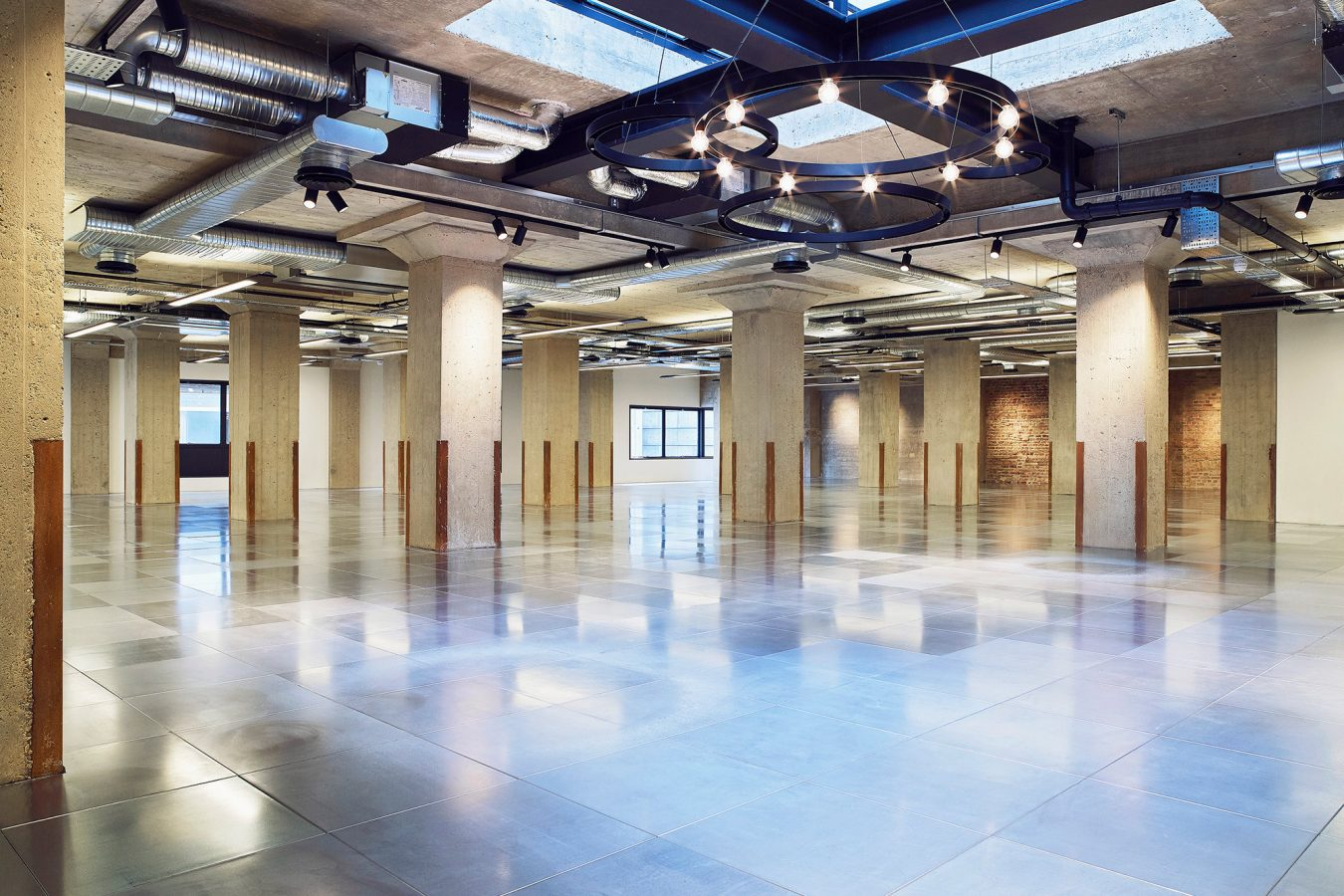 An office space redecorated with new flooring throughout industrial style lightning and exposed concrete pillions.