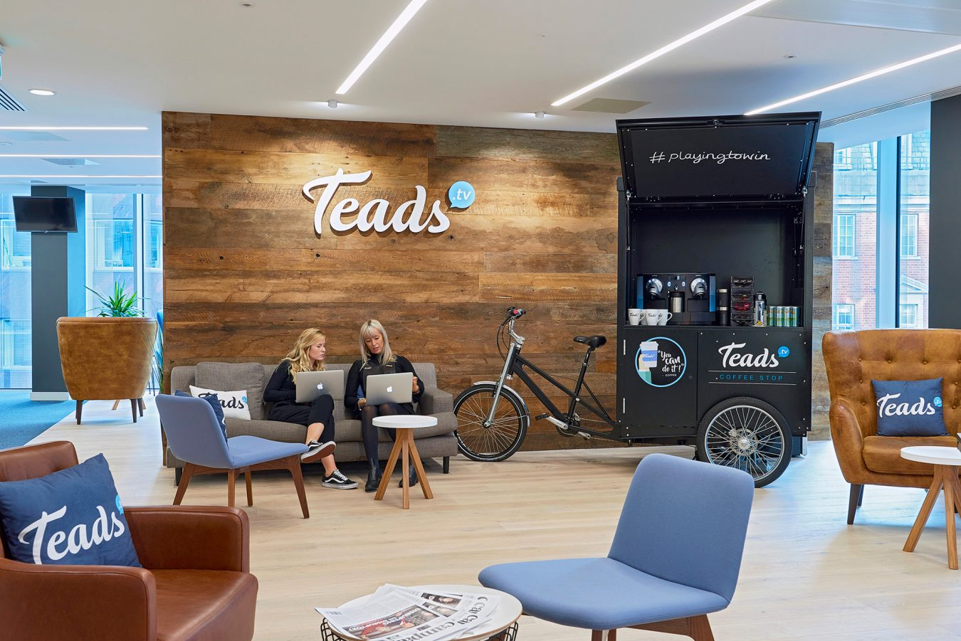 Modern office design and build for Teads reception and women working on their Apple Laptops.