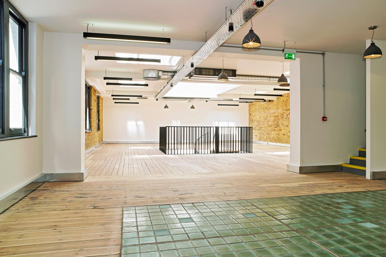 Reconditioned original building features in Diamond House such as brick walls, green tiles and hard wood floor.