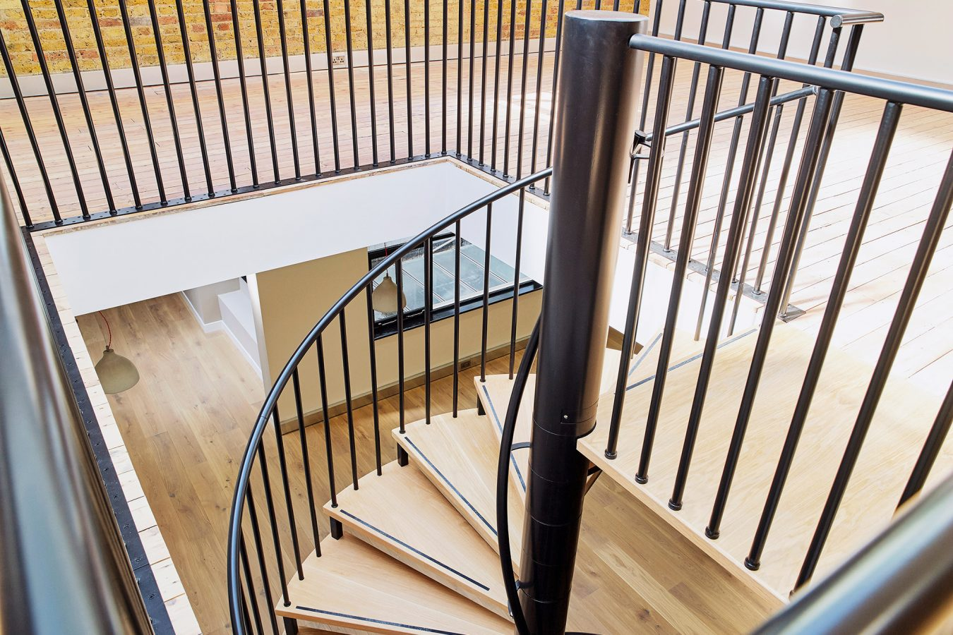 Cilindric metal and wood staircase for office space.