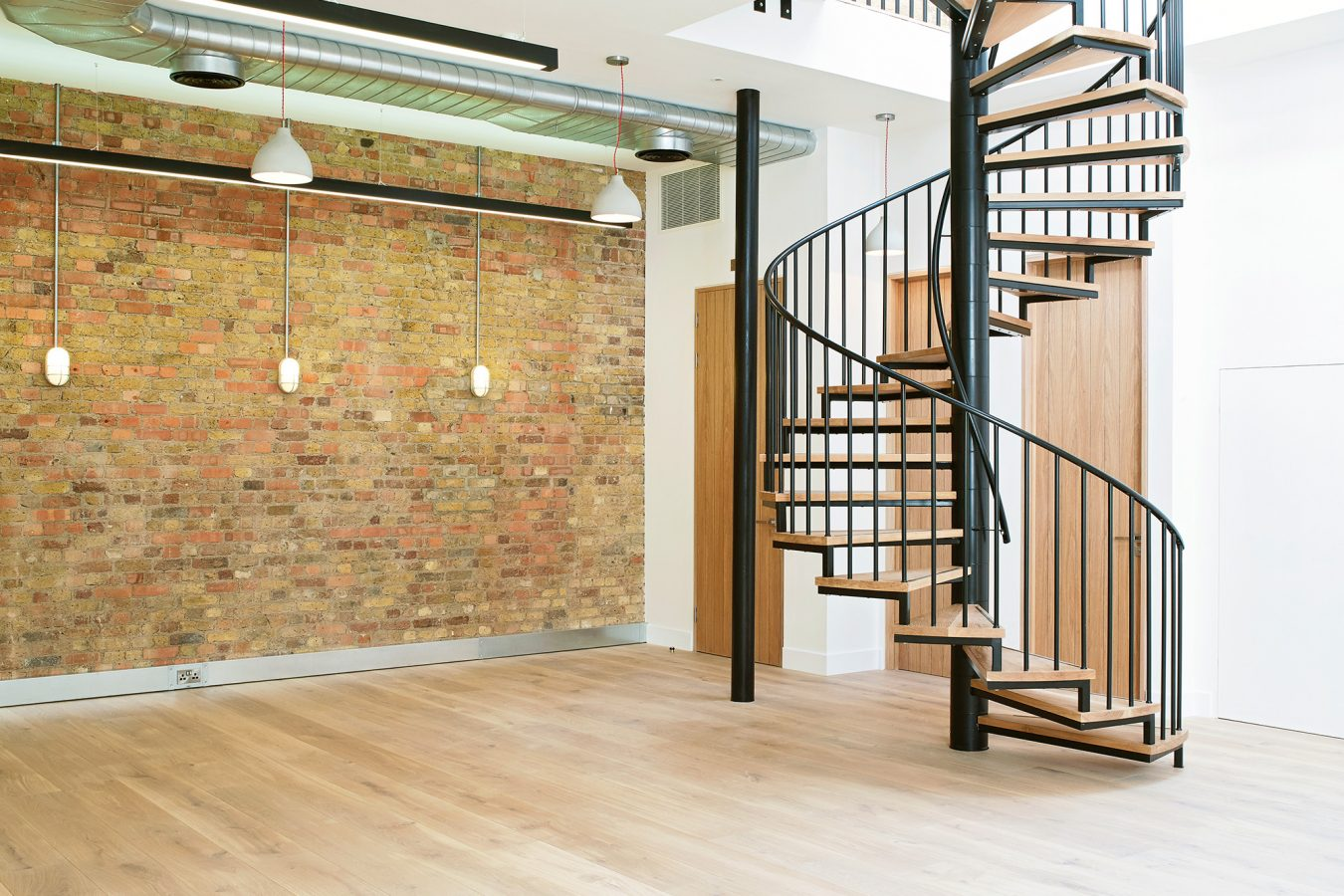 Feature brick wall exposed and cilindric staircase in an office space.