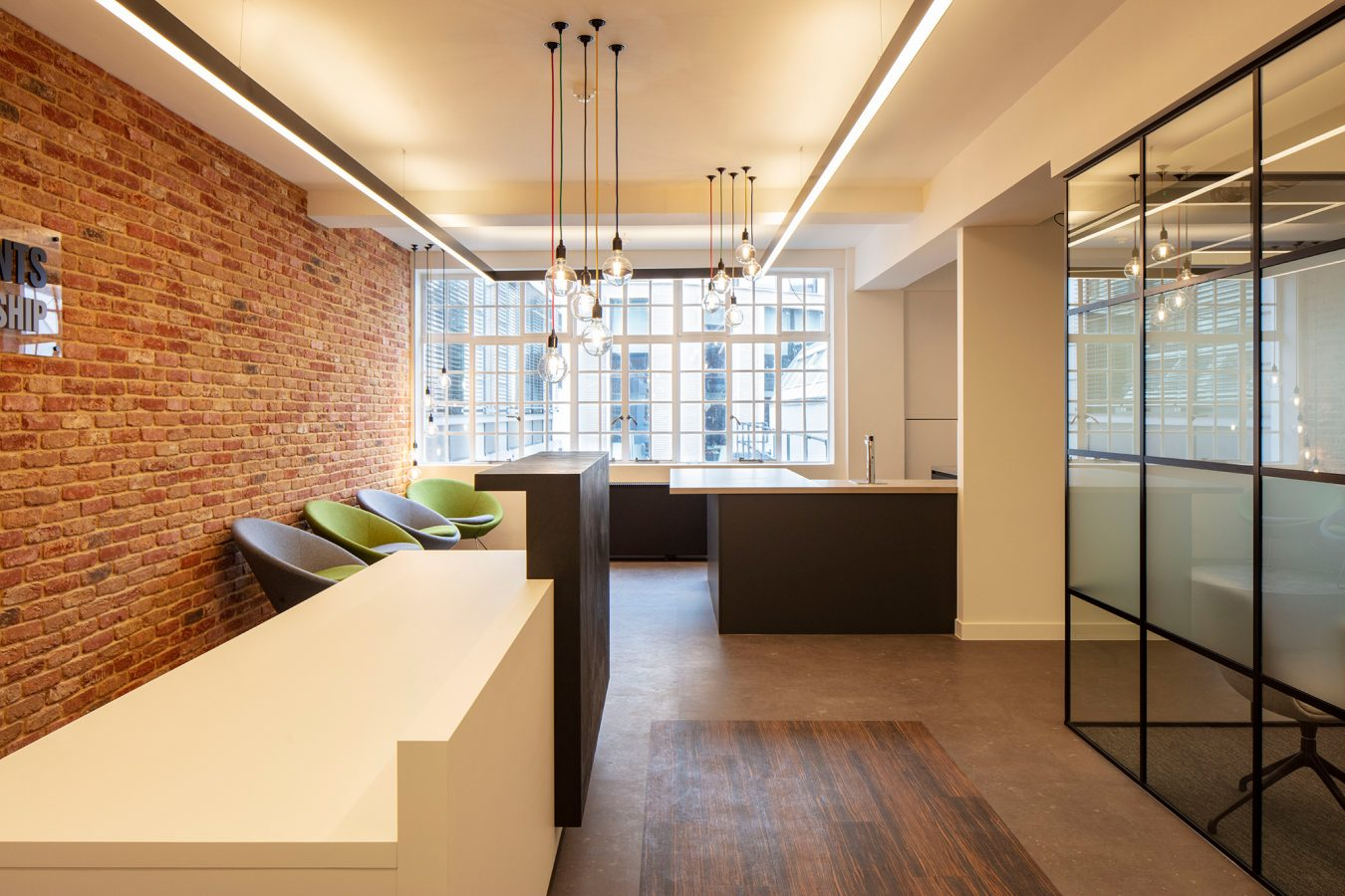 A refurbishment project including the reception area for office relocation, decorated with feature wall and pendant retro lights and crittal style glazed partitions for space optimisation. in Westminster City