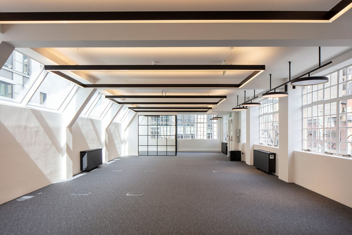 Empty office space open plan office layout with LED lighting and sash windows near London.