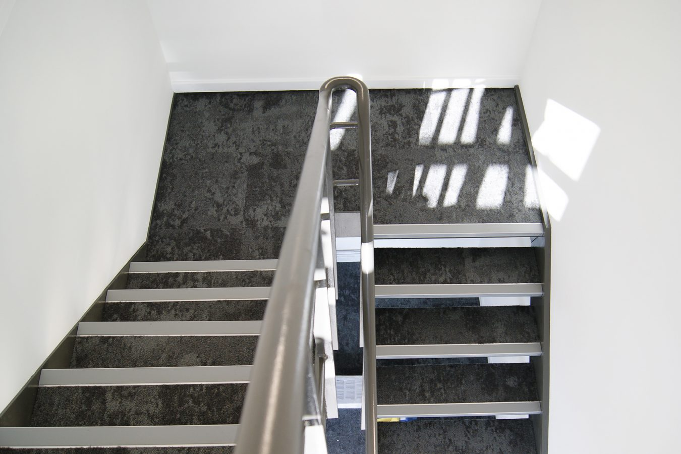 Reconditionated stairs with grey new carpet tiles in a warehouse workspace.