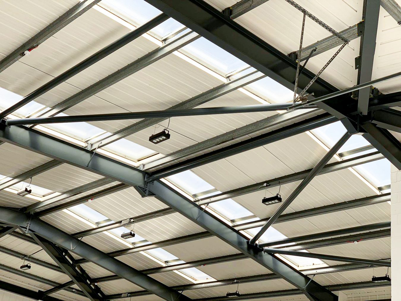 A warehouse refurbishment in Croydon, including the fit-out of a industrial roof structure. Suspended lights in warehouse roof to enhance brightness. Main building contractors in London.