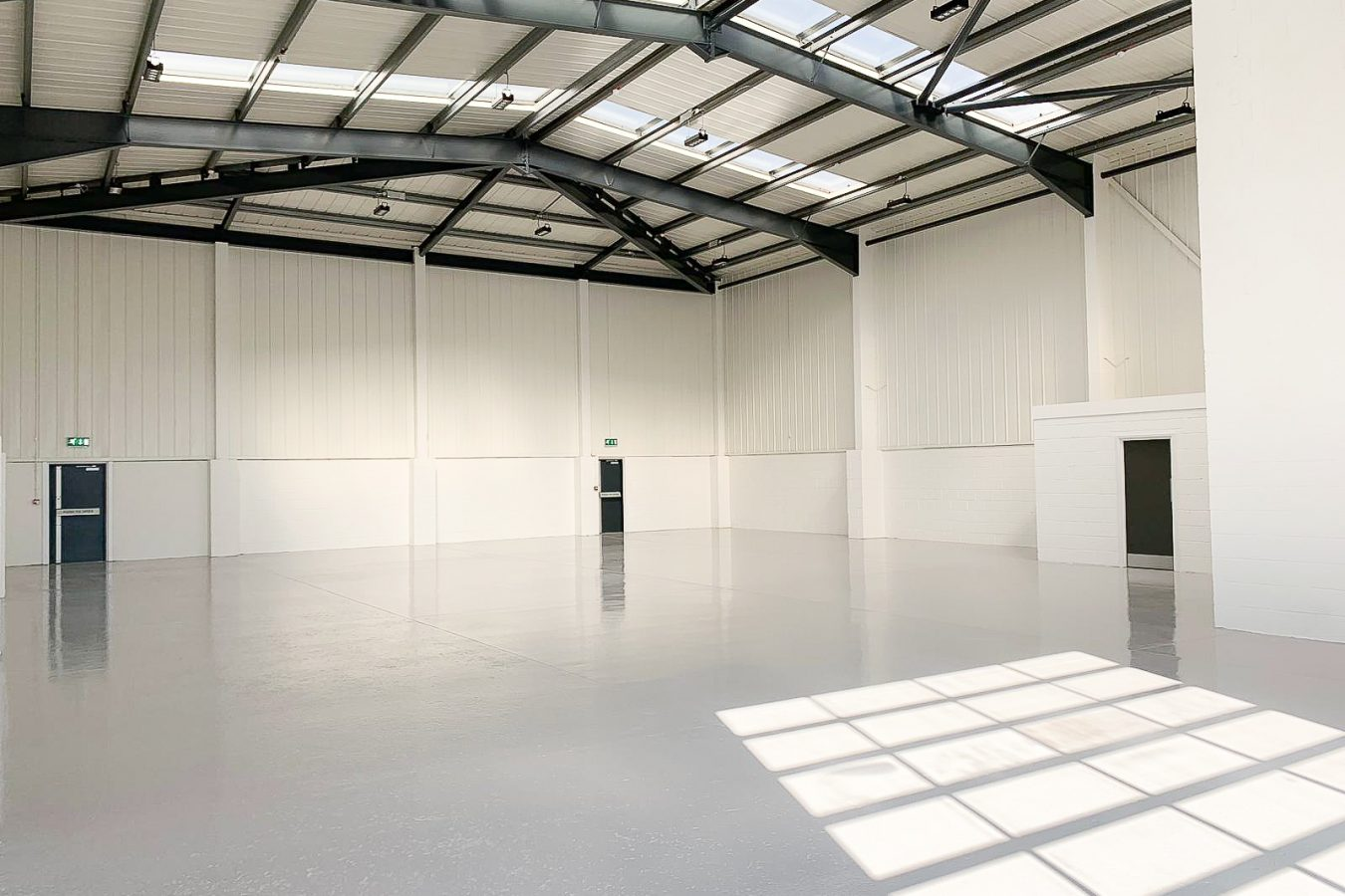 Industrial roof refurbishment on the structure and new flooring throughout the space in neutral colours.