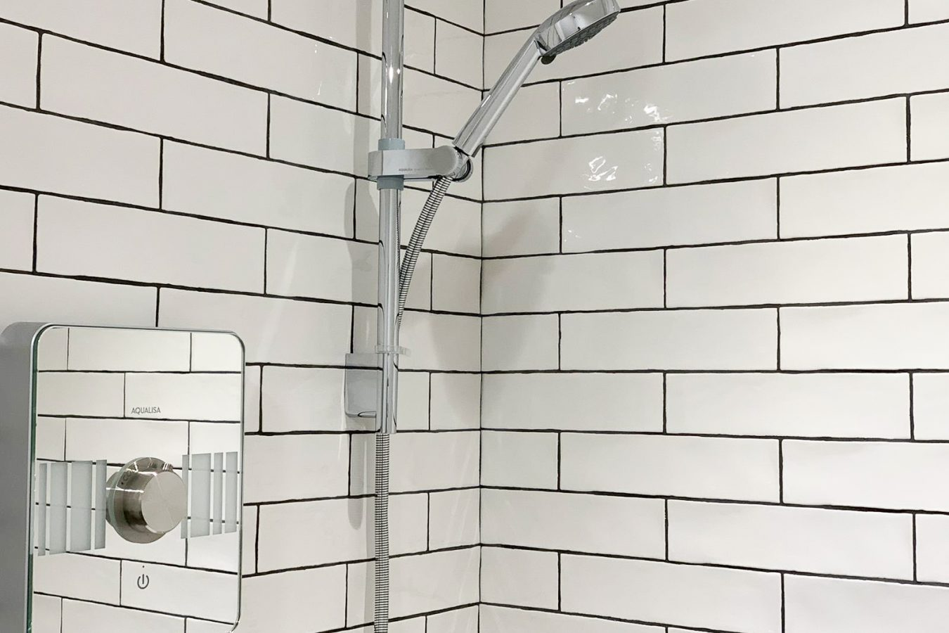 White tiles and silver shower in a new modern office bathroom.