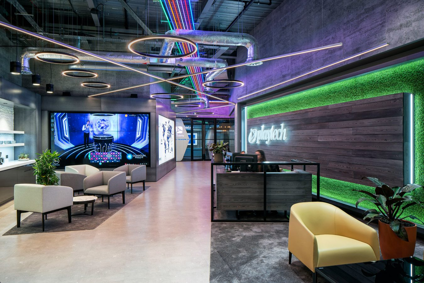 Industrial interior design for Playtech reception, decorated with coloured way finding LED lights, minimal furniture design and opulent carpet.
