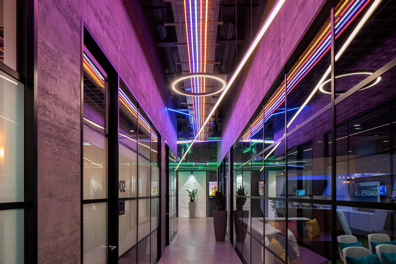Industrial style design for office halloway and glazed doors and partitions, and coloured LED lights.