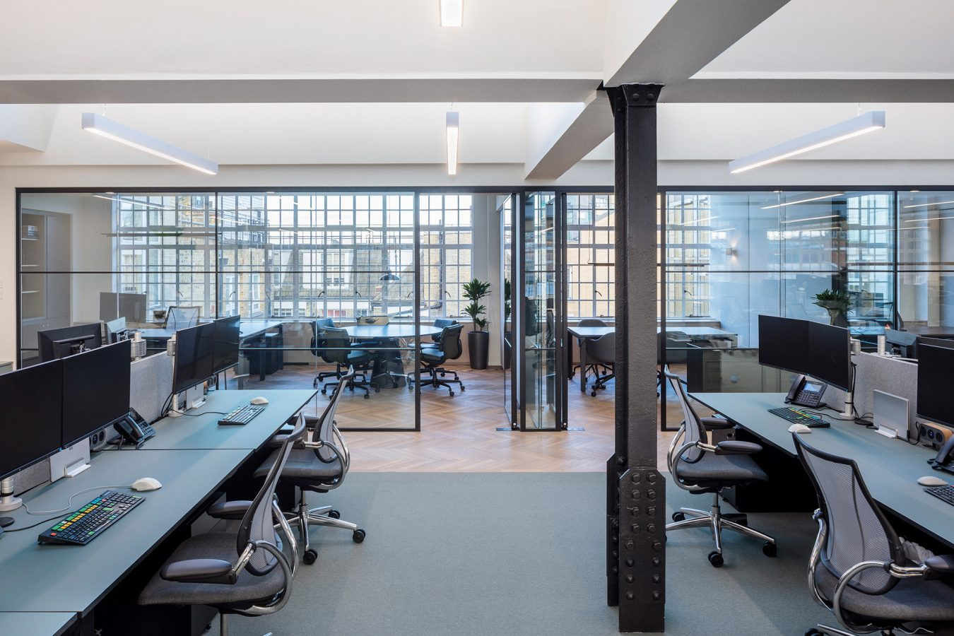 Open plan work-space decorated with wood floor tiles and multiple meeting rooms divided by glazed glass partitions.