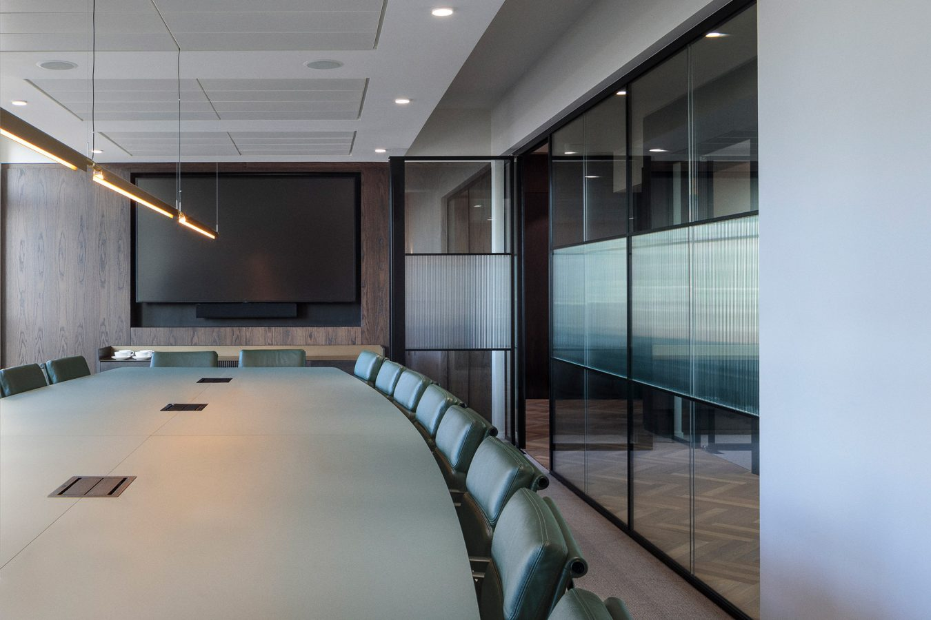Large boardroom table and leather green chairs for an office space in London.