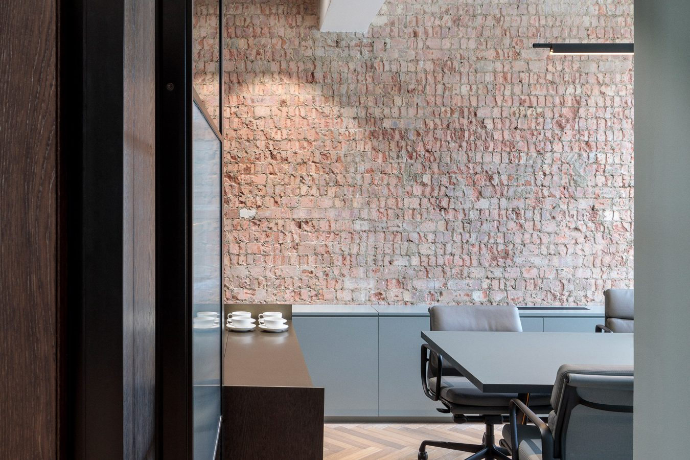 Feature wall with exposed brickwork in an office meeting room.