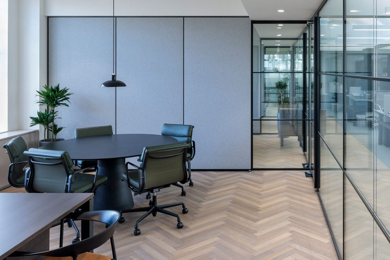 Meeting room designed with parquet floor tiles and glazed partitions.