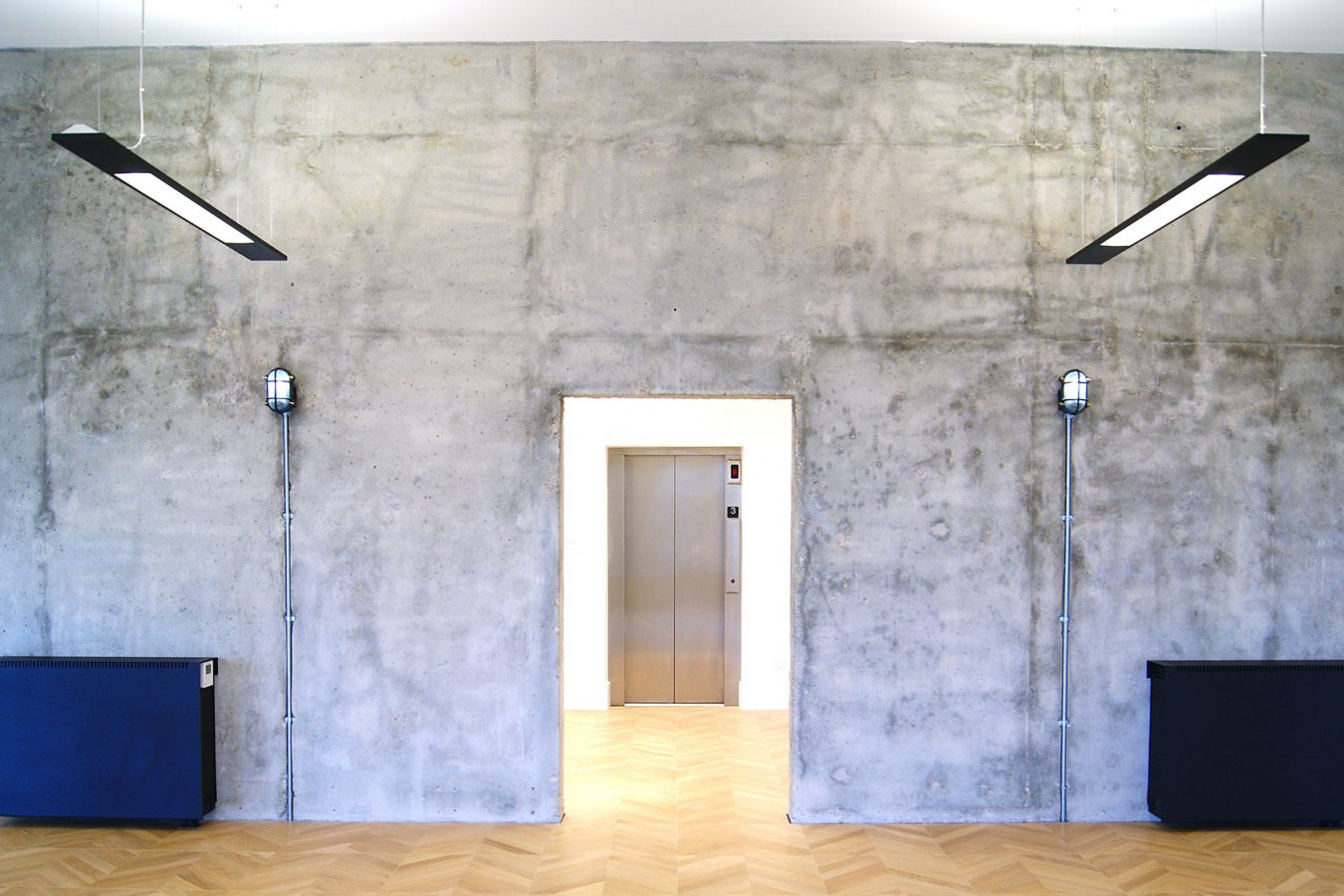 Concrete wall and industrial style lights in an office space in South Lambeth Road