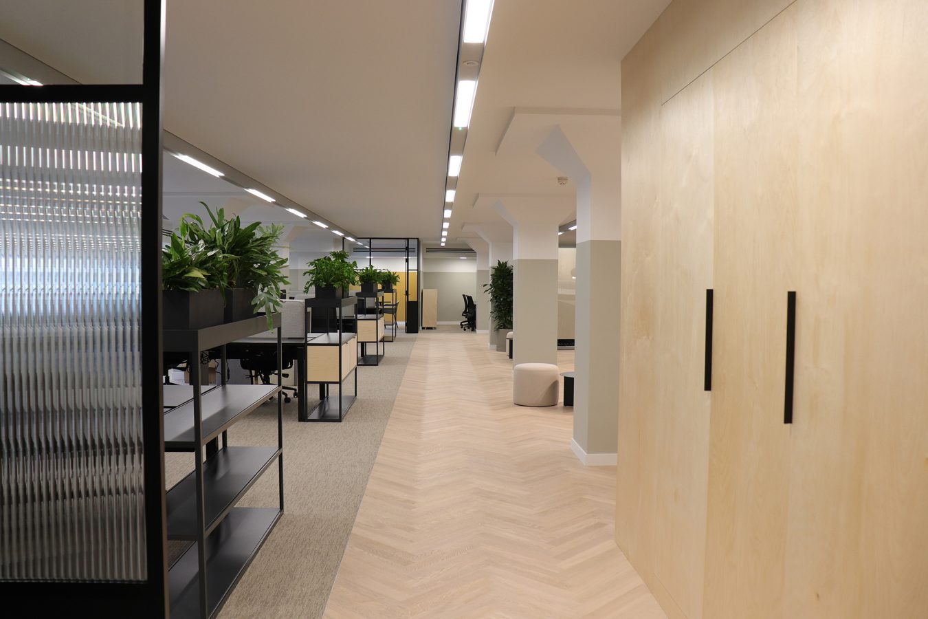 Plug and play scheme in a workplace decorated with neutral parquet flooring, open plan workspace and wooden storage wall.